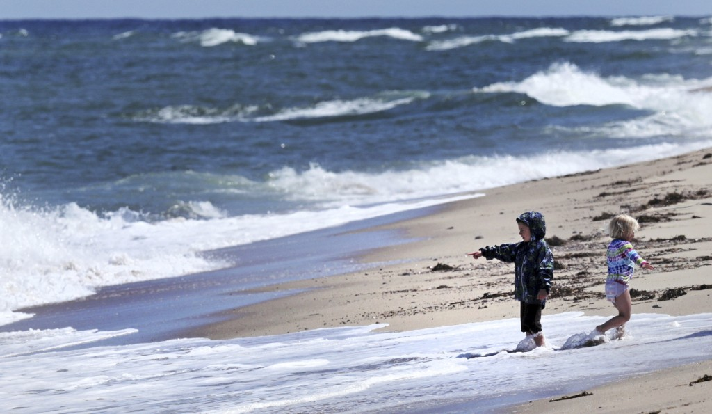 In this May 22, 2019, photo, two children play in the surf at Newcomb Hollow Beach, where a boogie boarder was bitten by a shark and later died of his