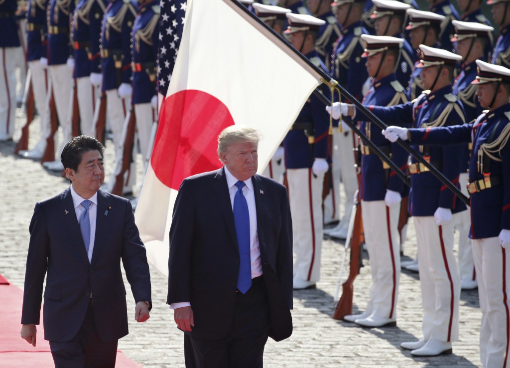 FILE - In this Nov. 6, 2017, file photo, U.S. President Donald Trump, second from left, reviews an honor guard during a welcome ceremony, escorted by ...