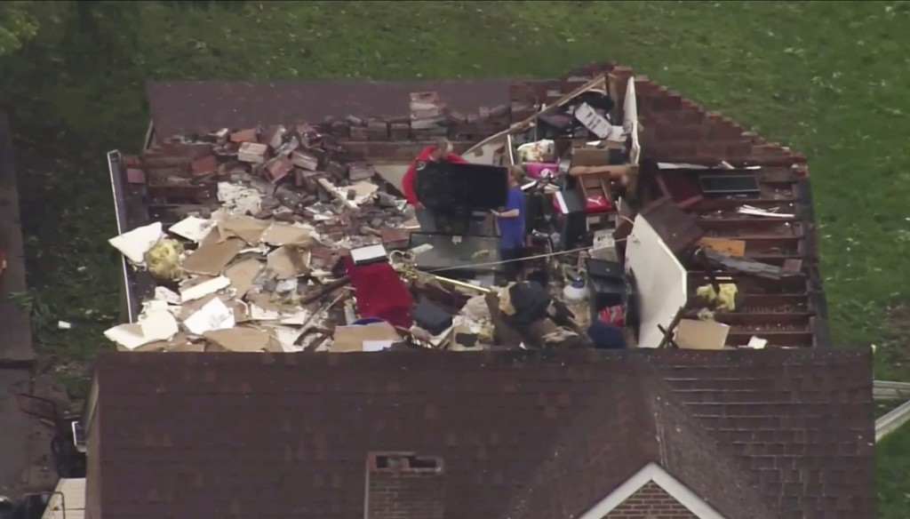 This still image provided by KMOV-TV shows people going through their belongings after a tornado destroyed the roof of their home on Thursday, May 23,...
