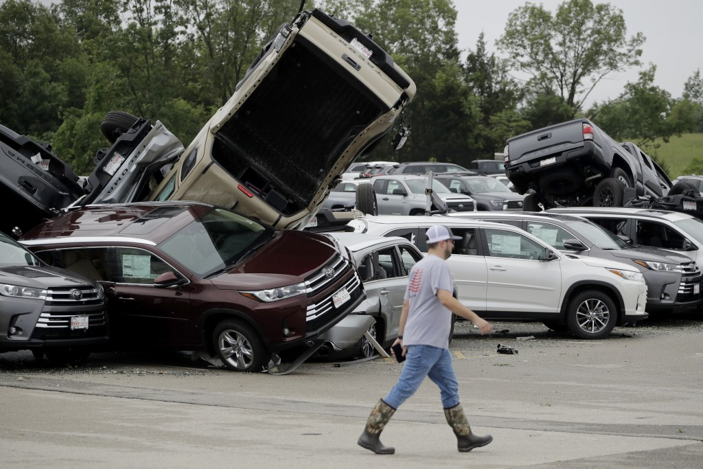 A worker walks past tornado-damaged Toyotas at a dealership in Jefferson City, Mo., Thursday, May 23, 2019, after a tornado tore though late Wednesday...