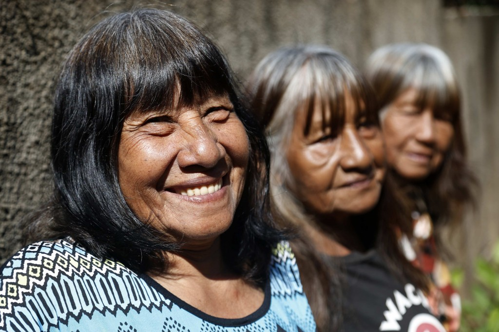 Maka indigenous leader-in-training Tsiweyenki, whose Spanish name is Gloria Elizeche, smiles with her sisters Cristina, center, and Estela as they coo