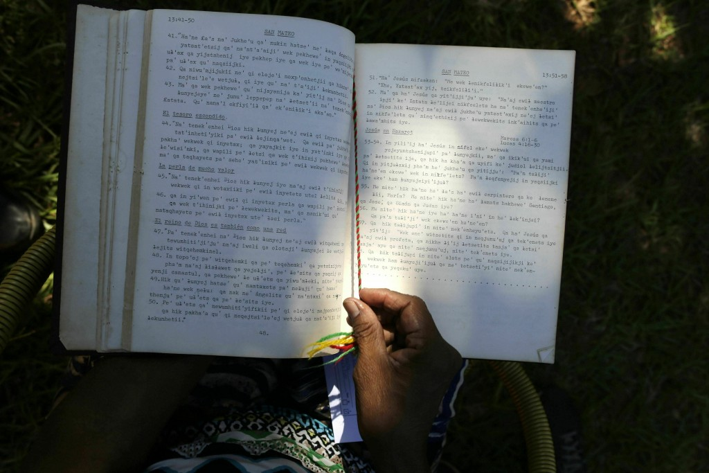 The hands of Maka indigenous leader-in-training Tsiweyenki, or Gloria Elizeche in Spanish, handles a copy of the Bible translated into her native lang