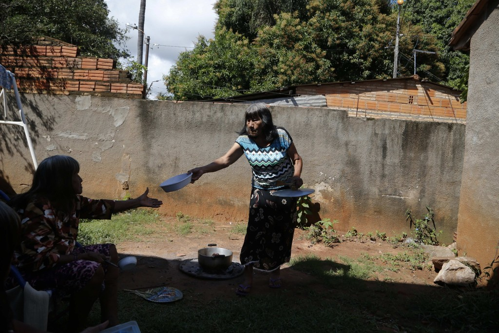 Maka indigenous leader-in-training Tsiweyenki, or Gloria Elizeche in Spanish, passes a plate to her sister Cristina as they cook in her backyard in Ma
