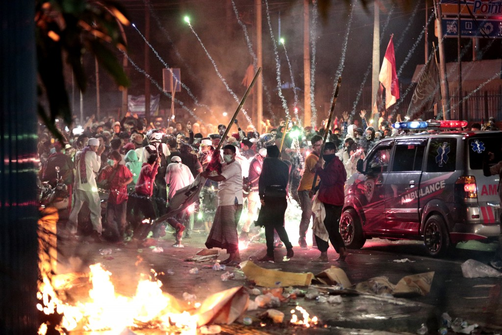 In this Wednesday, May 22, 2019, file photo, firecrackers explode near supporters of presidential candidate Prabowo Subianto during clashes with the p...