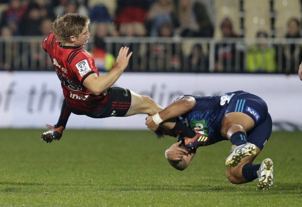 Crusaders Jack Goodhue, left, is airborne as he is tackled by Blues Levi Aumua during their Super Rugby match in Christchurch, New Zealand, Saturday, ...