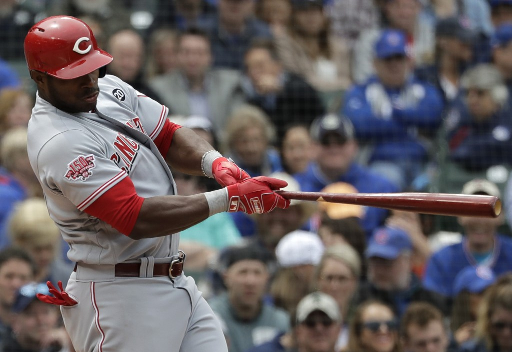 Cincinnati Reds' Yasiel Puig hits an RBI single against the Chicago Cubs during the fourth inning of a baseball game Friday, May 24, 2019, in Chicago....