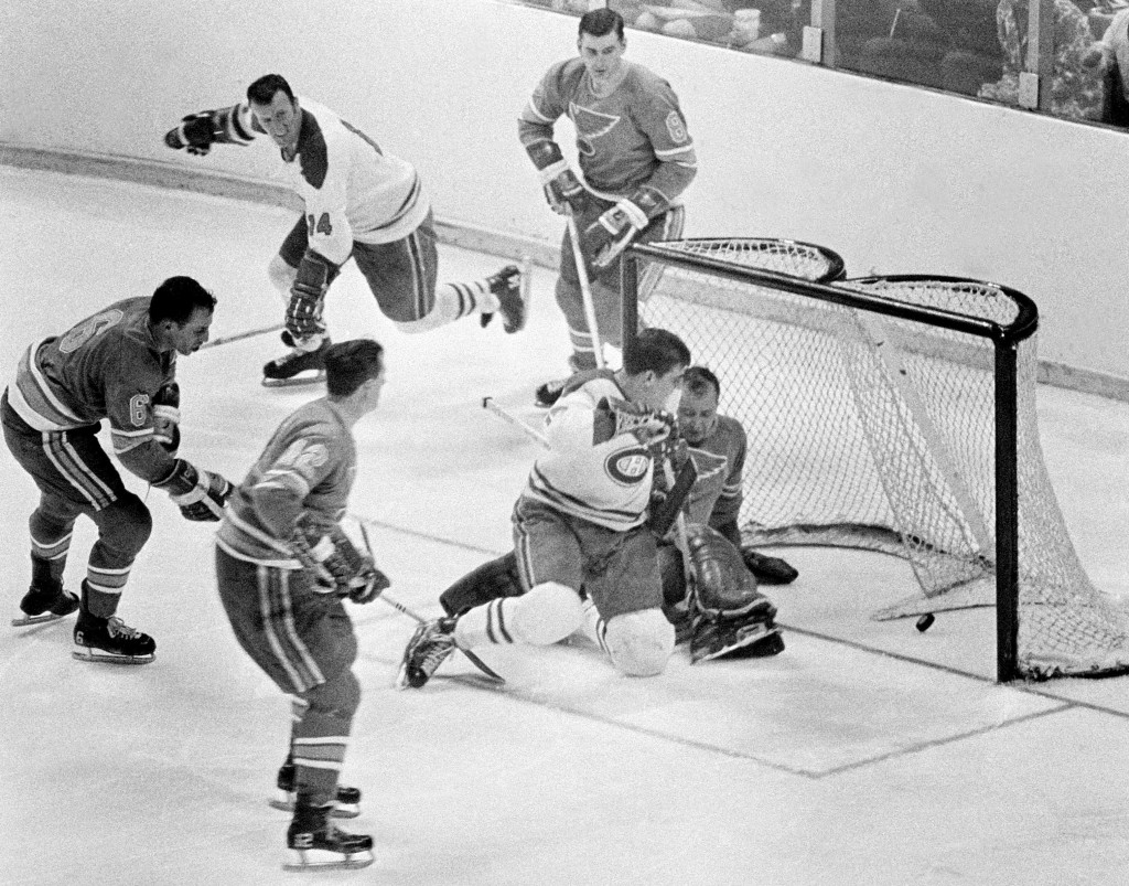FILE - Intis May 7, 1968, file photo, Montreal Canadiens' Serge Savard is about to land in the lap of St. Louis Blues' goalie Glenn Hall as the puck s...