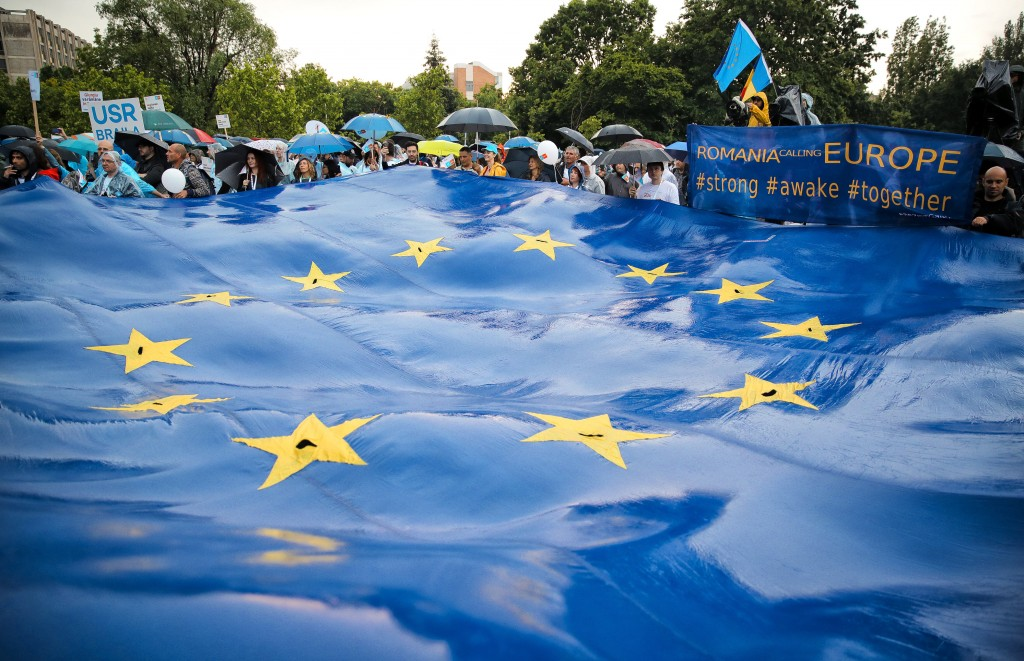 Romanians wave a large EU flag during a 2020 USR PLUS alliance European Parliament elections rally, in Bucharest, Romania, Friday, May 24, 2019. Roman