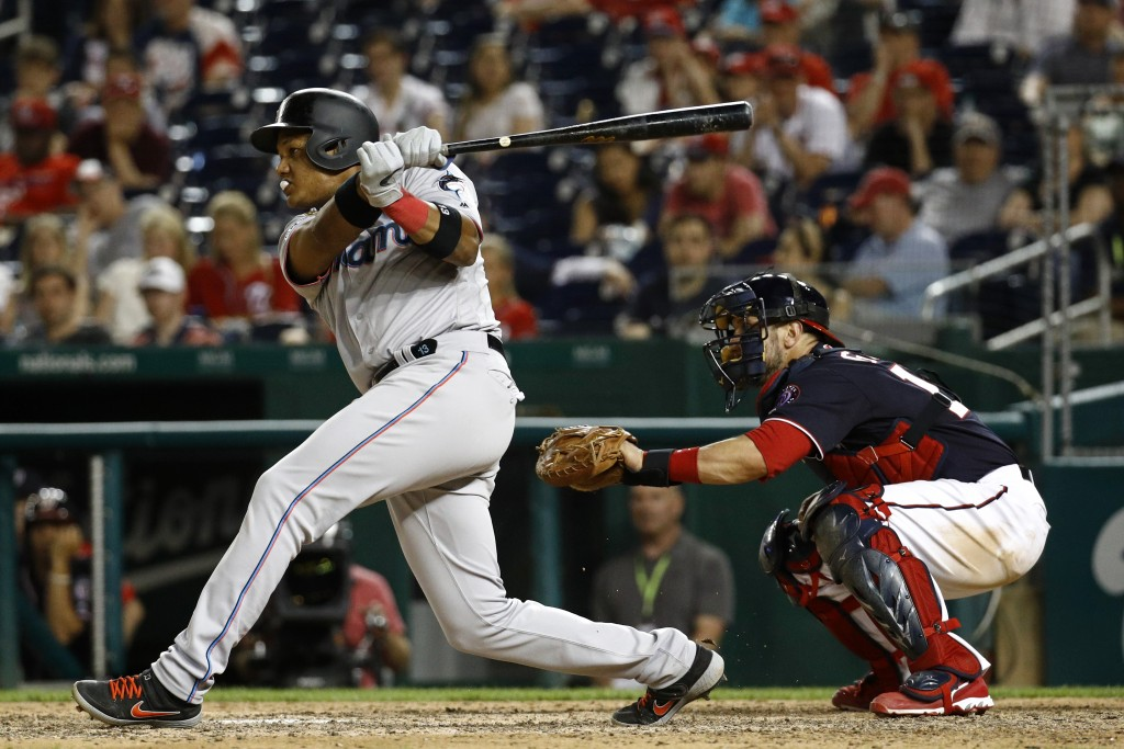 Miami Marlins' Starlin Castro, left, singles in front of Washington Nationals catcher Yan Gomes in the eighth inning of a baseball game, Friday, May 2...