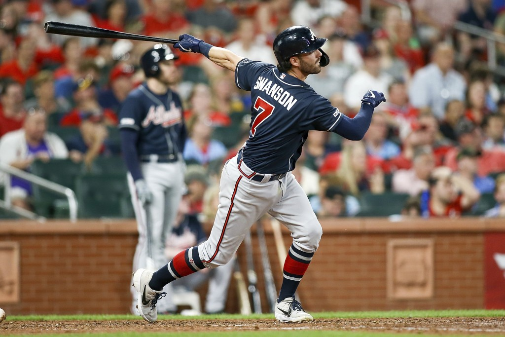 Atlanta Braves' Dansby Swanson follows through on a two-run home run during the eighth inning of a baseball game against the St. Louis Cardinals, Frid