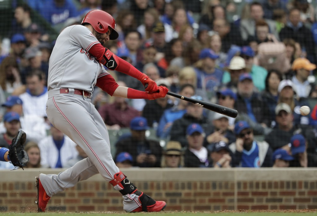 Cincinnati Reds' Jesse Winker hits a one-run double against the Chicago Cubs during the seventh inning of a baseball game Friday, May 24, 2019, in Chi...