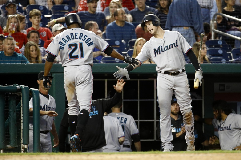 Miami Marlins' Brian Anderson, right, greets teammate Curtis Granderson after Granderson hit a solo home run in the fourth inning of a baseball game a...