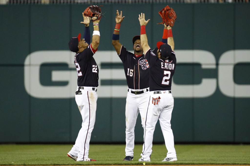 From left to right, Washington Nationals outfielders Juan Soto, Victor Robles and Adam Eaton celebrate after a baseball game against the Miami Marlins...