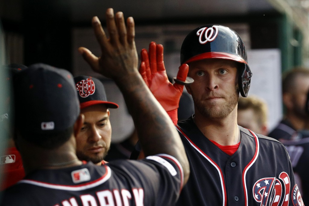 Washington Nationals' Kyle McGowin, right, high-fives teammate Howie Kendrick after scoring on Adam Eaton's groundout in the third inning of a basebal...