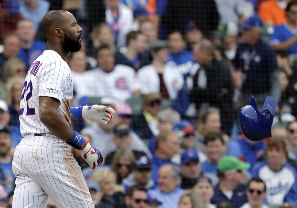Chicago Cubs' Jason Heyward throws his helmet after striking out swinging during the fifth inning of a baseball game against the Cincinnati Reds, Frid...