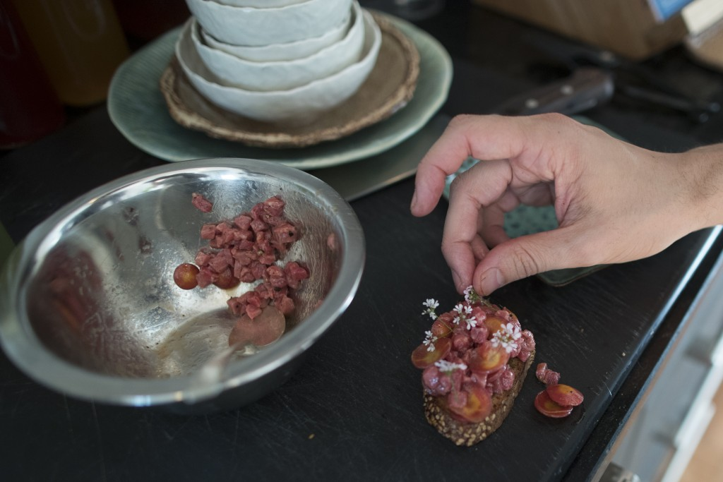 In this May 17, 2019 photo, Jonah Reider prepares a beef tartare toast appetizer during a Pith dinner in New York. Reider's informal kitchen training ...