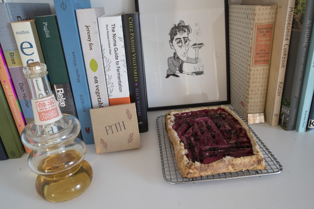 In this May 17, 2019 photo, a rhubarb tart is displayed with a caricature of Jonah Reider and his cookbooks in his New York apartment. In the competit...