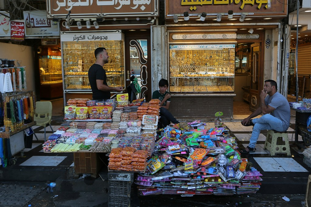 In this Wednesday, May 21, 2019, photo, street vendors and shop owners wait for customers outside the shrine of Imam Moussa al-Kadhim in Kadhimiya dis