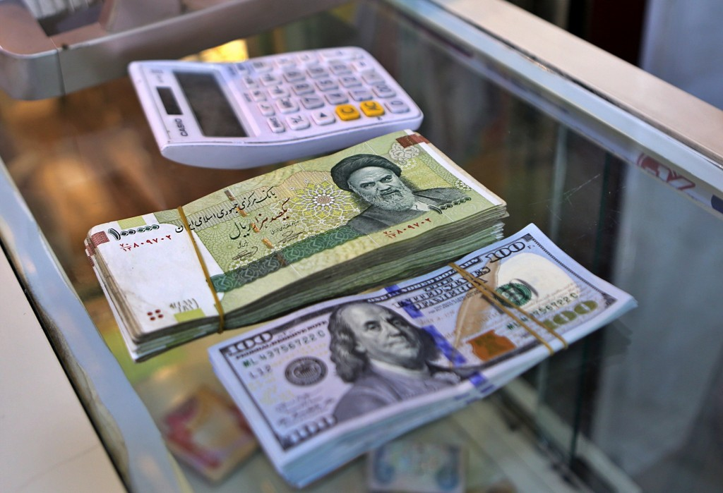 In this Wednesday, May 21, 2019, photo, U.S. and Iranian currency are readied by a money exchanger outside the golden-domed shrine of Imam Moussa al-K