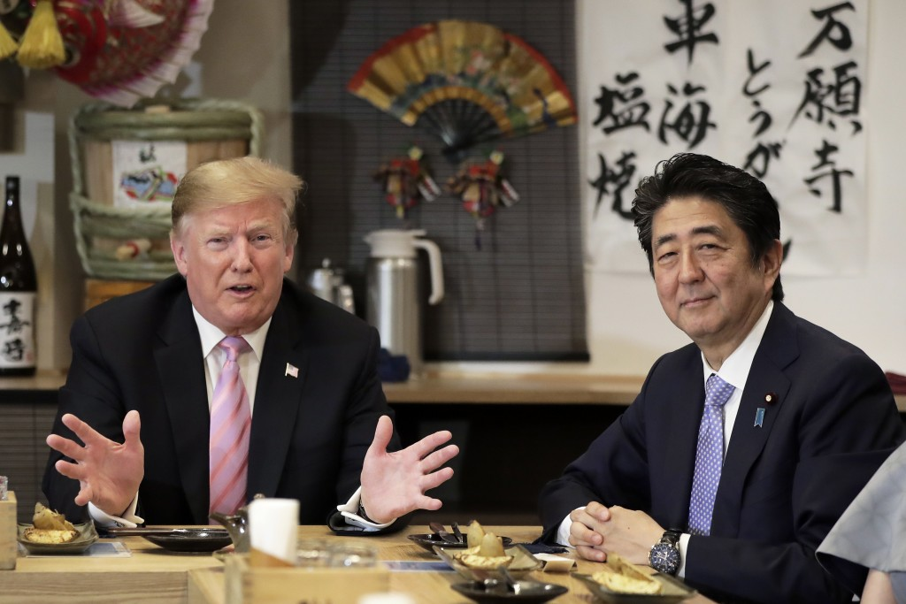 U.S. President Donald Trump, left, speaks as he dines with Japan's Prime Minister Shinzo Abe at the Inakaya restaurant in the Roppongi district of Tok...