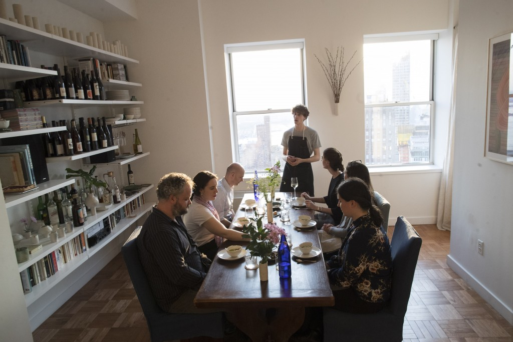 In this May 17, 2019 photo, Jonah Reider, center, talks to his guests about the dinner he is serving them in his New York apartment. His new mission: ...