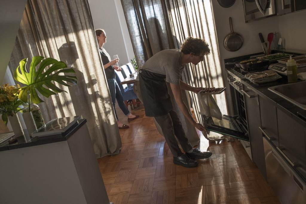 In this May 17, 2019 photo, guests have drinks and appetizers while Jonah Reider, right, checks on the entrees in his oven at his New York apartment. ...