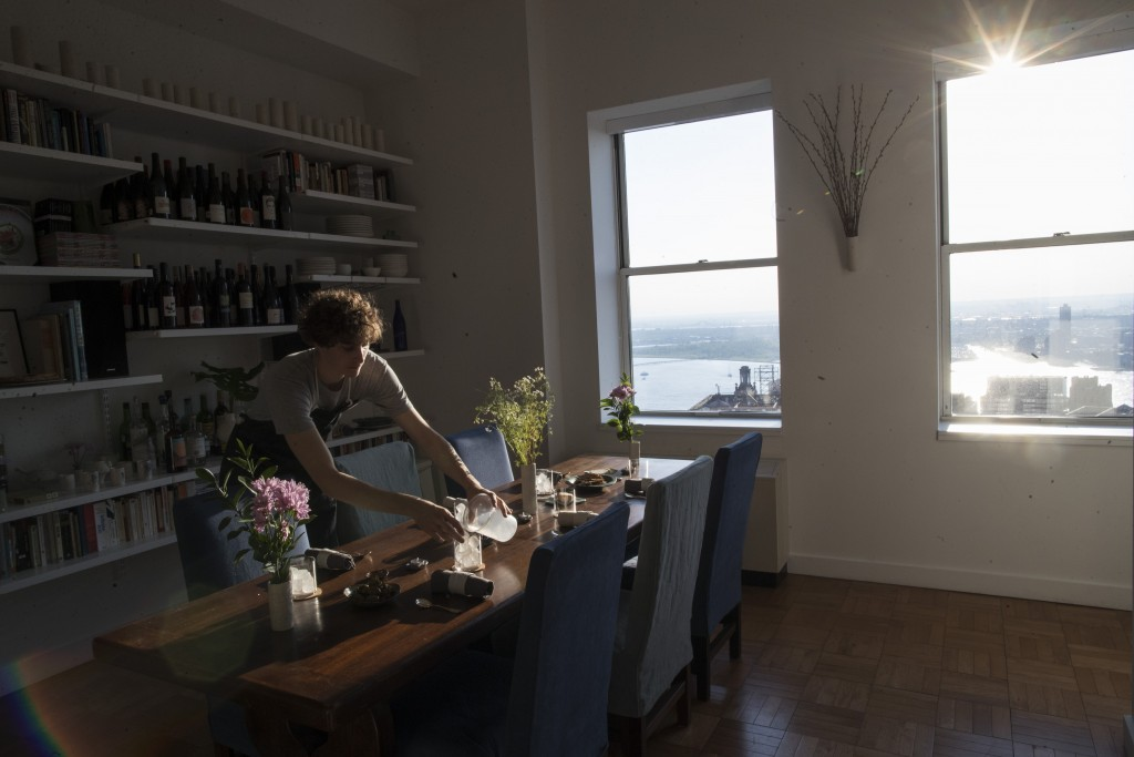In this May 17, 2019 photo, Jonah Reider sets the table before dinner guests arrive in New York. His apartment has a view of New York Harbor and the S...