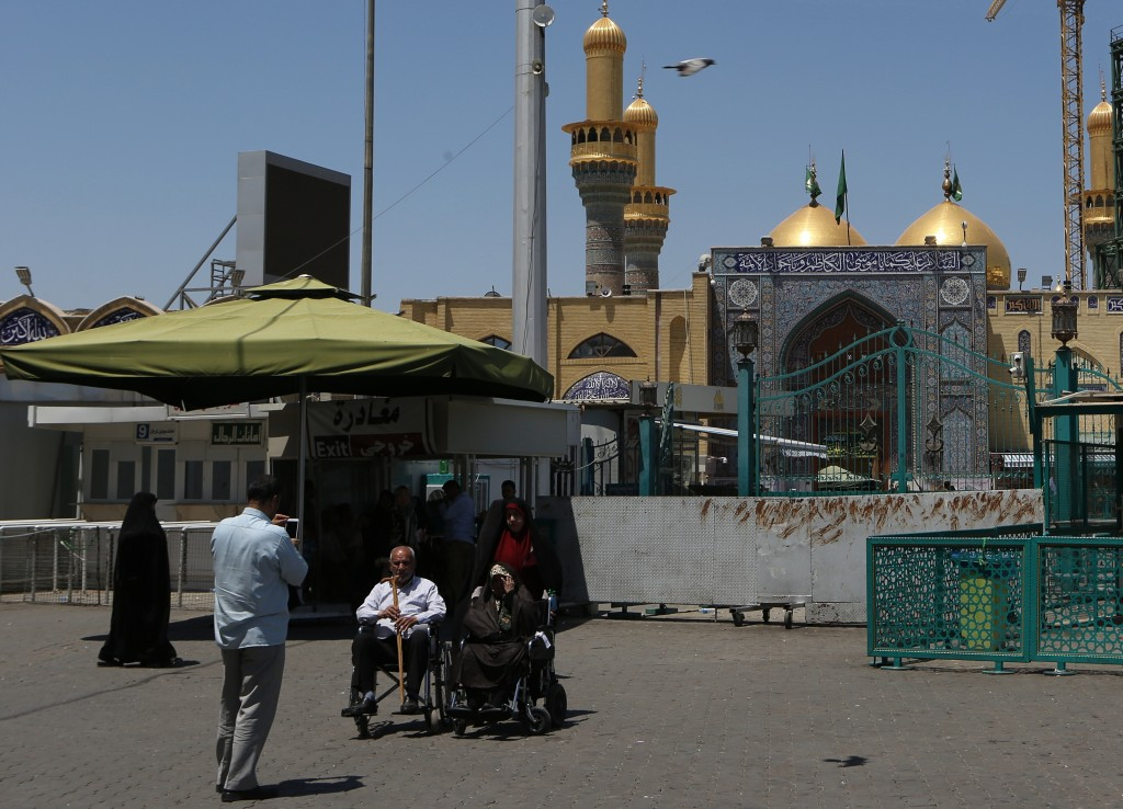 In this Wednesday, May 21, 2019, photo, Shiite pilgrims visit the shrine of Imam Moussa al-Kadhim in Kadhimiya district in north Baghdad, Iraq. Many s