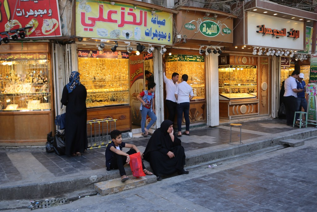 In this Wednesday, May 21, 2019, photo, street vendors and shop owners wait for customers outside the shrine of Imam Moussa al-Kadhim in Kadhimiya dis...