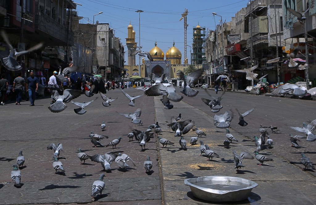 In this Wednesday, May 21, 2019, photo, pigeons fly outside the golden-domed shrine of Imam Moussa al-Kadhim in Kadhimiya district in north Baghdad, I
