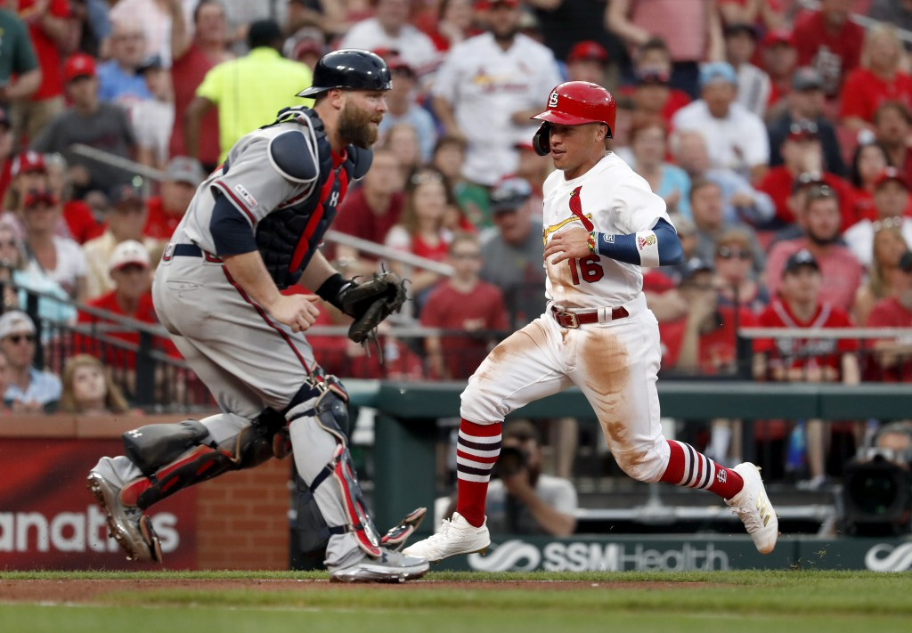 St. Louis Cardinals' Kolten Wong, right, scores past Atlanta Braves catcher Brian McCann during the fourth inning of a baseball game Sunday, May 26, 2...