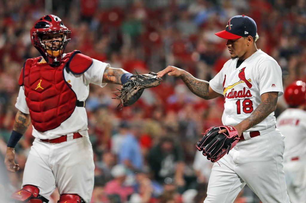 St. Louis Cardinals starting pitcher Carlos Martinez, right, is congratulated by catcher Yadier Molina after getting Atlanta Braves' Dansby Swanson to