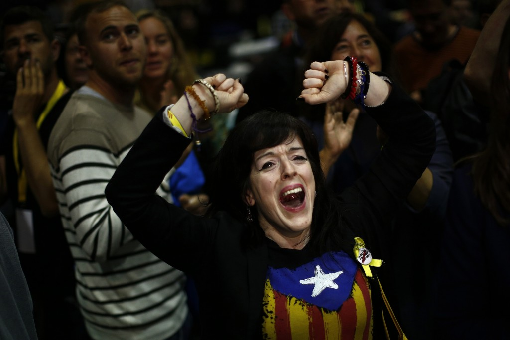 """A woman wearing an """"estelada"""" or independence flag reacts at the Esquerra Republicana of Catalonia party headquarters in Barcelona, Spain, Sunday, May..."""