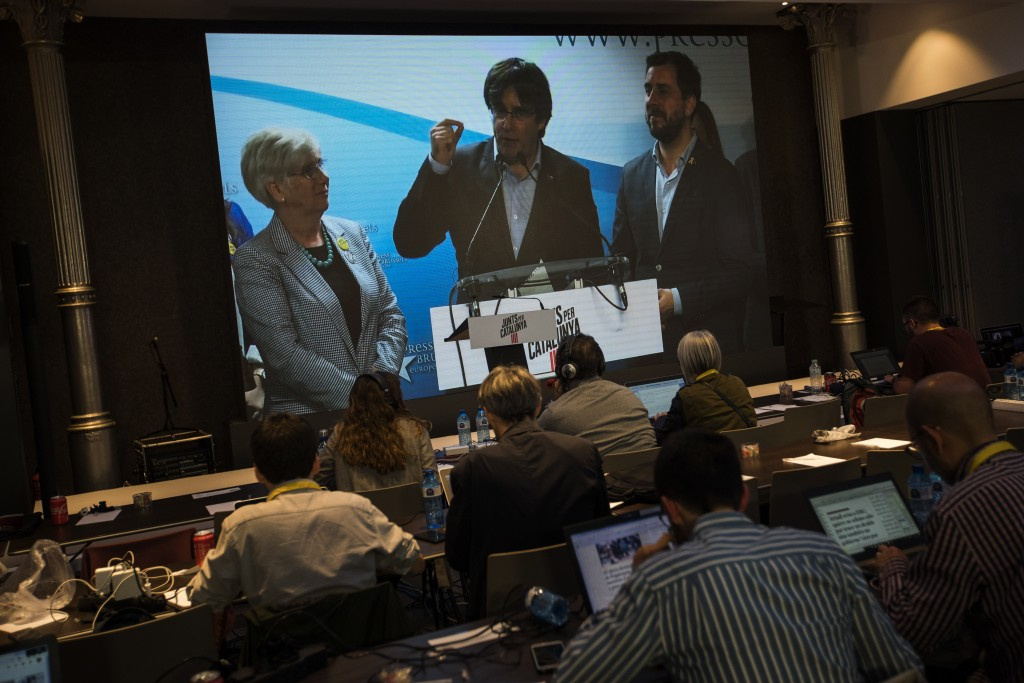 Former regional Catalan President Carles Puigdemont appears on a screen during a video conference from Brussels, at the party headquarters in Barcelon...