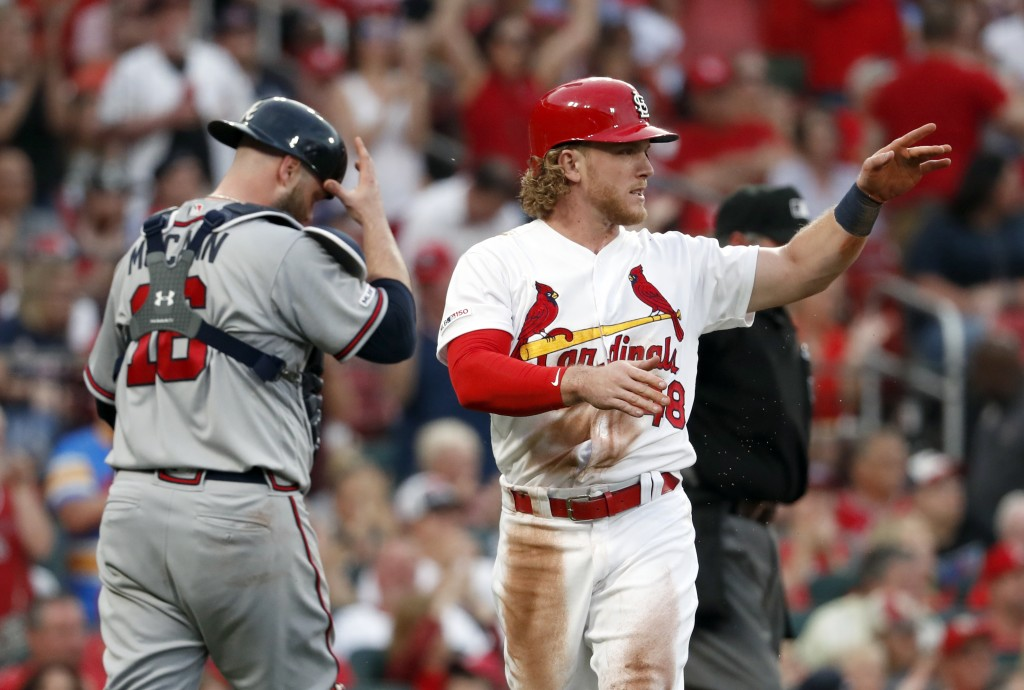 St. Louis Cardinals' Harrison Bader, right, celebrates after scoring as Atlanta Braves catcher Brian McCann walks back to the plate during the fourth