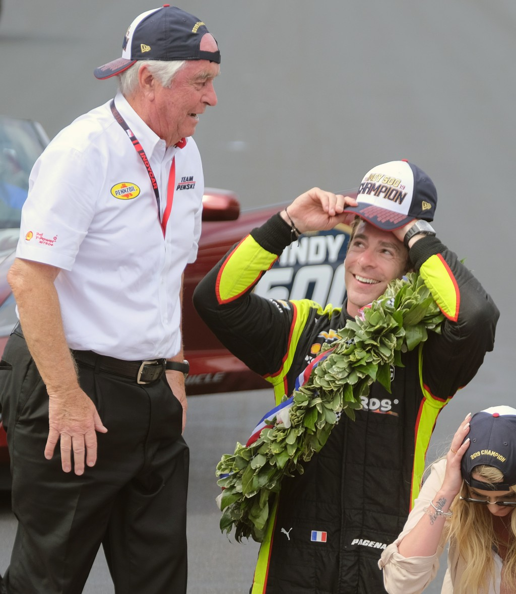 Simon Pagenaud, of France, talks with car owner Roger Penske as they celebrate on the Yard of Bricks after Pagenaud won the Indianapolis 500 IndyCar a...
