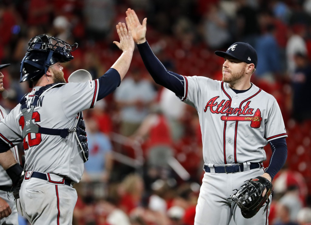 Atlanta Braves' Freddie Freeman, right, and Brian McCann celebrate a 4-3 victory over the St. Louis Cardinals in a baseball game, Sunday, May 26, 2019