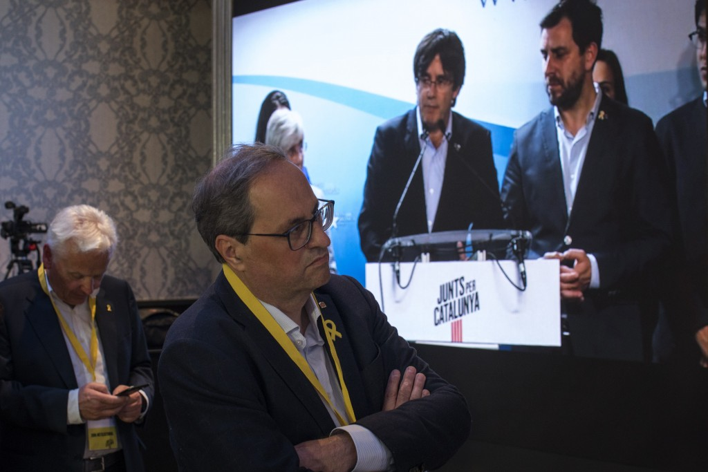 Regional Catalan President Quim Torra, centre, looks at former regional Catalan President Carles Puigdemont appearing on a screen during a video confe...