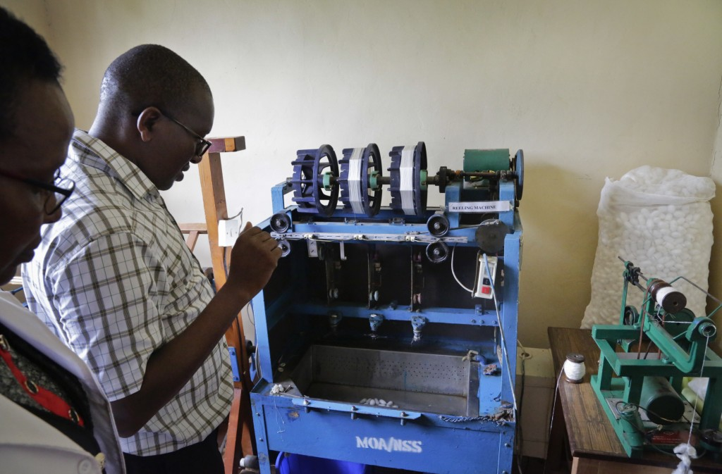 In this photo taken Friday, April 26, 2019, Director of the National Sericulture Research Center, Muo Kasina, demonstrates a silk reeling machine at t...