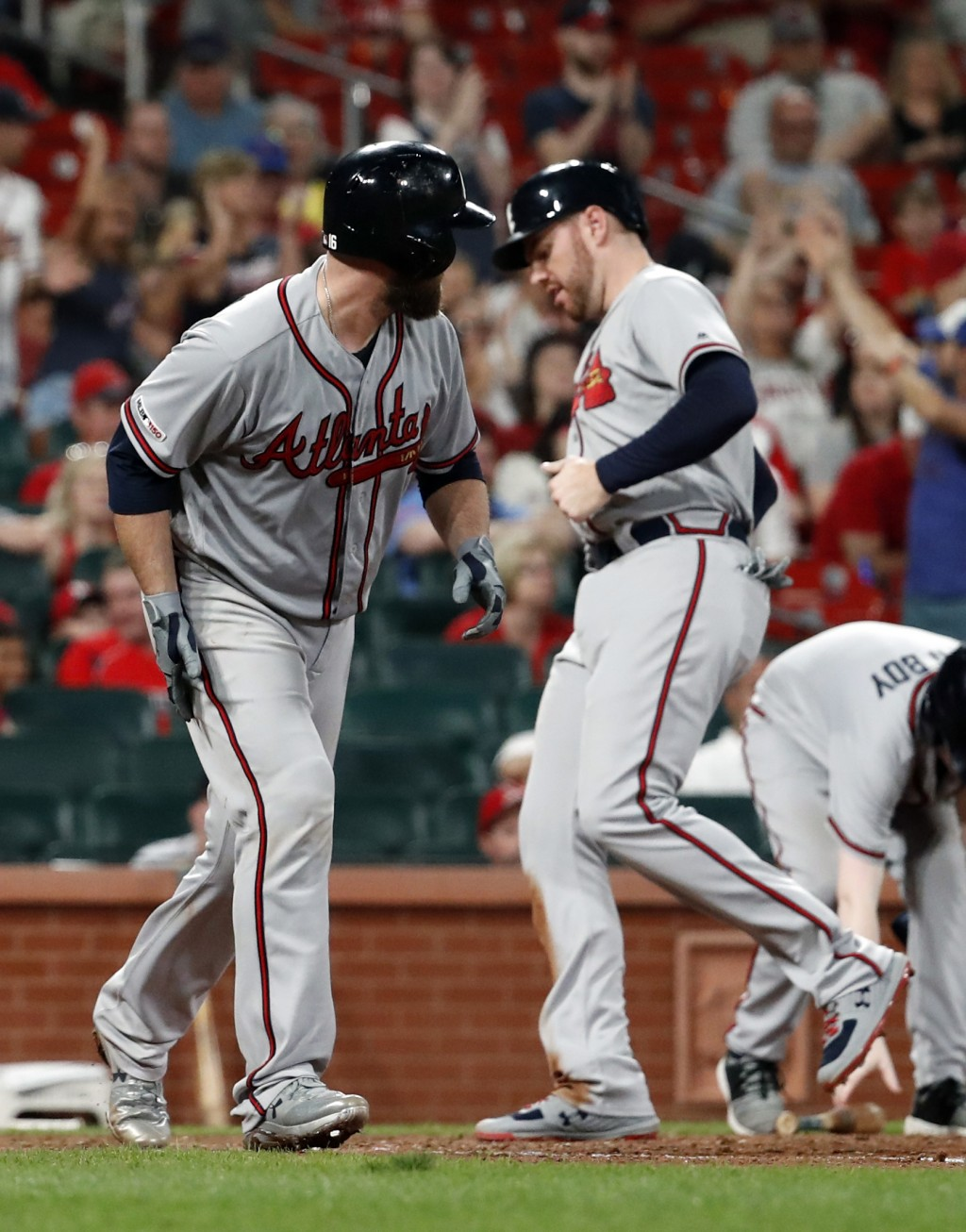 Atlanta Braves' Brian McCann, left, takes his base on a bases-loaded walk as Freddie Freeman scores during the 10th inning of a baseball game against