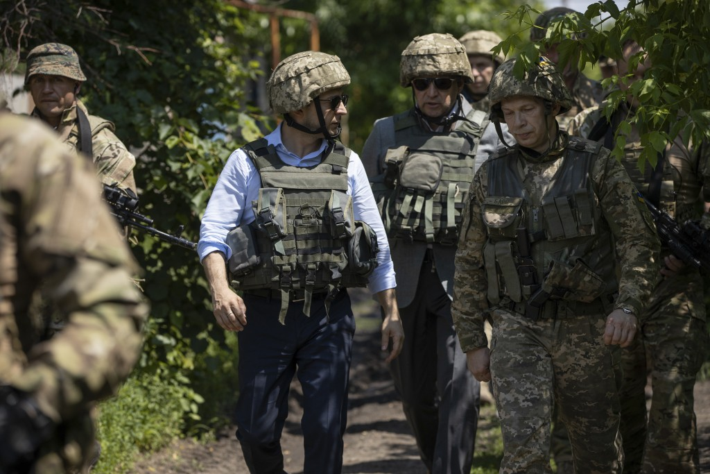 Ukrainian President Volodymyr Zelenskiy talks with servicemen as he visits the war-hit Luhansk region, eastern Ukraine, Monday, May 27, 2019. (Ukraini