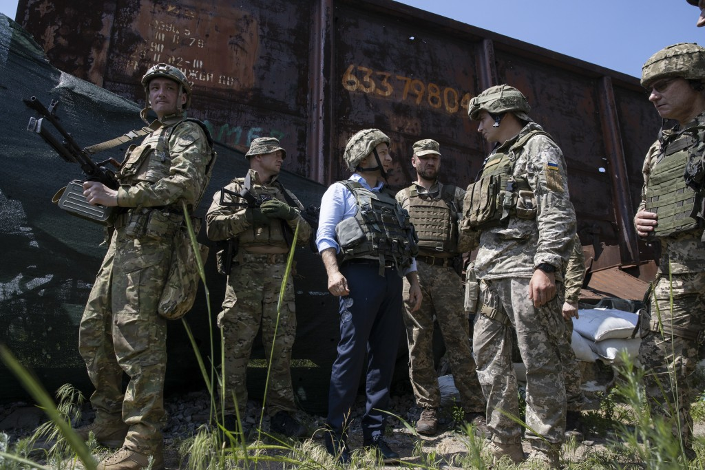 Ukrainian President Volodymyr Zelenskiy, center, talks with servicemen as he visits the war-hit Luhansk region, eastern Ukraine, Monday, May 27, 2019....