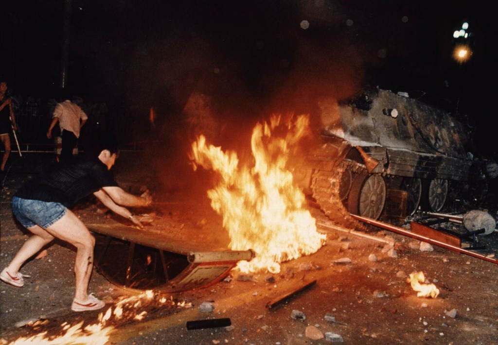 FILE - In this June 4, 1989 file photo, a student protester puts barricades in the path of an already burning armored personnel carrier that rammed th