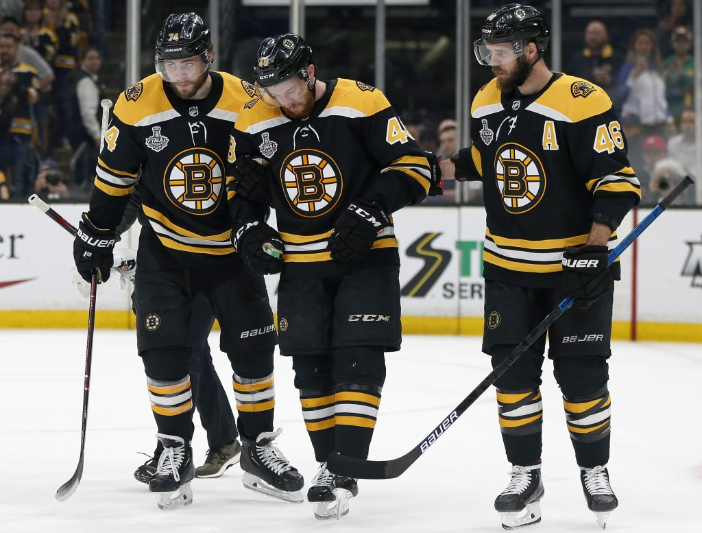 Boston Bruins' Matt Grzelcyk, center, is assisted from the ice by Jake DeBrusk, left, and David Krejci, right, after an injury during the first period