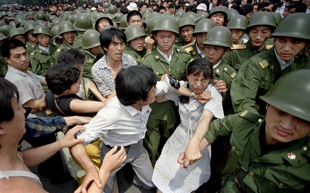 FILE - In this June 3, 1989 file photo, a young woman is caught between civilians and Chinese soldiers, who were trying to remove her from an assembly