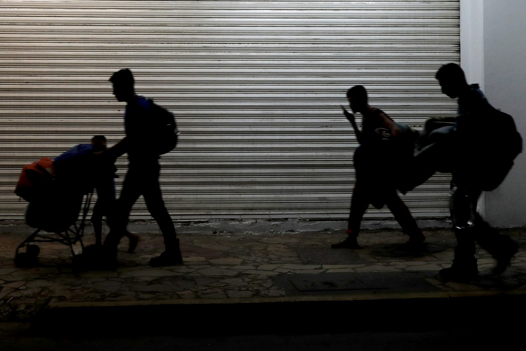 Migrant families camped in a park leave in the middle of the night as they are pushed out by Mexican immigration authorities, in Tapachula, Mexico, ea...