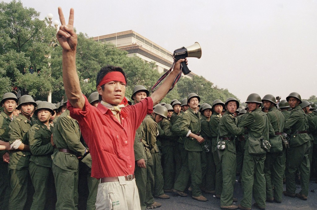 FILE - In this Saturday, June 3, 1989 file photo, a student pro-democracy protester flashes victory signs to the crowd as People's Liberation Army tro