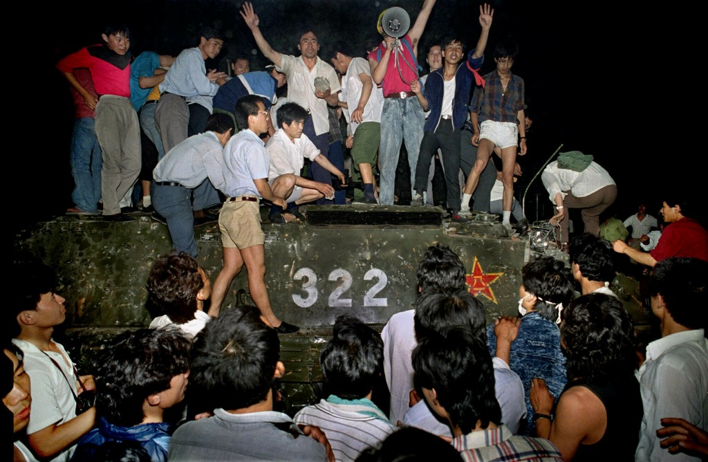 FILE - In this early June 4, 1989, file photo, civilians hold rocks as they stand on a government armored vehicle near Changan Boulevard in Beijing. O