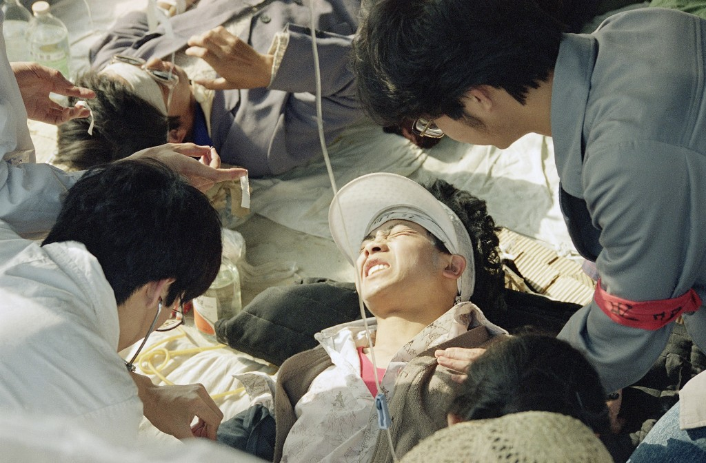 FILE - In this May 17, 1989 file photo, a striking Beijing University student is given first aid by medics at a field hospital in Tiananmen Square at