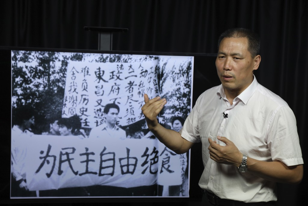 In this May 22, 2019, photo, Pu Zhiqiang recalls his experience near a photo which showed him taking part in the 1989 pro-democracy protest near a ban...